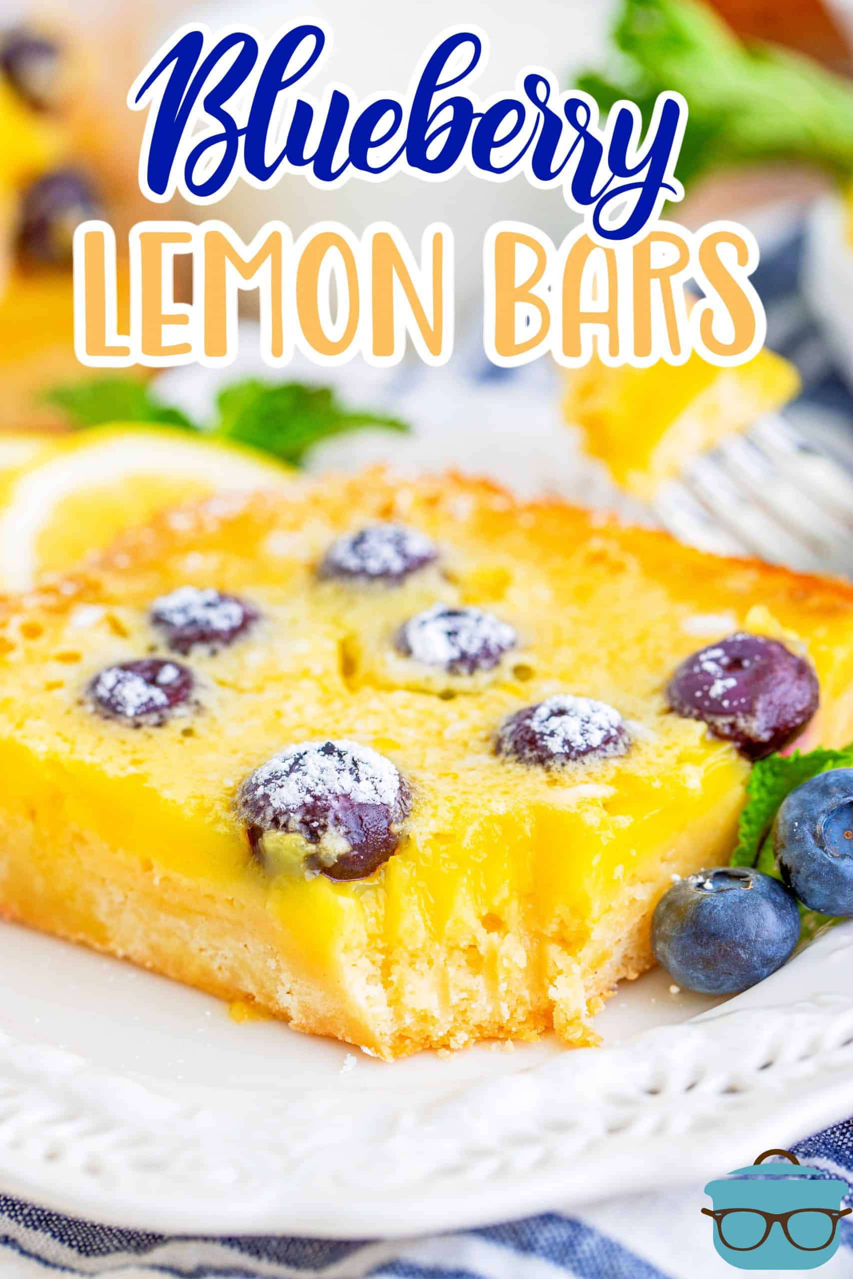 Close up of a bite taken out of one Blueberry Lemon bar with blueberries on white plate.
