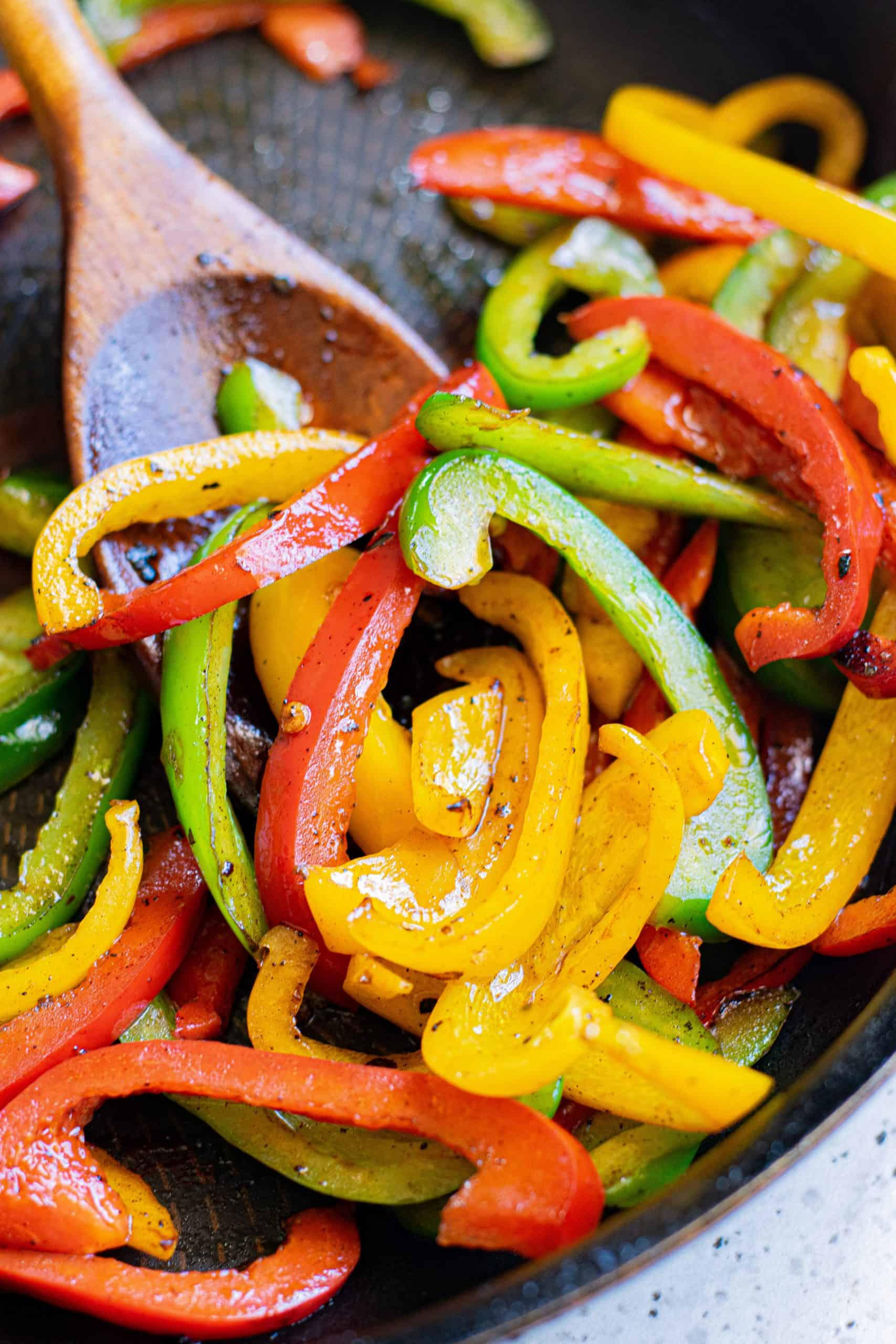 Peppers being cooked in pan.