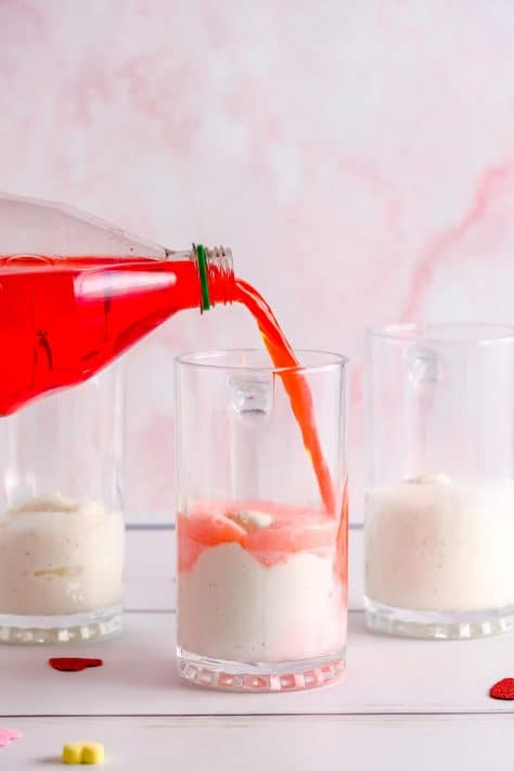 Soda being poured over ice cream in glass