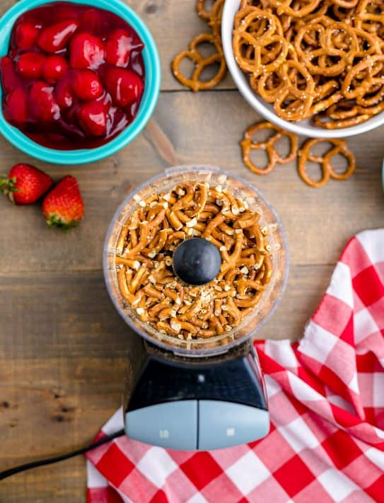 Overhead of pretzels in food processor on wooden table