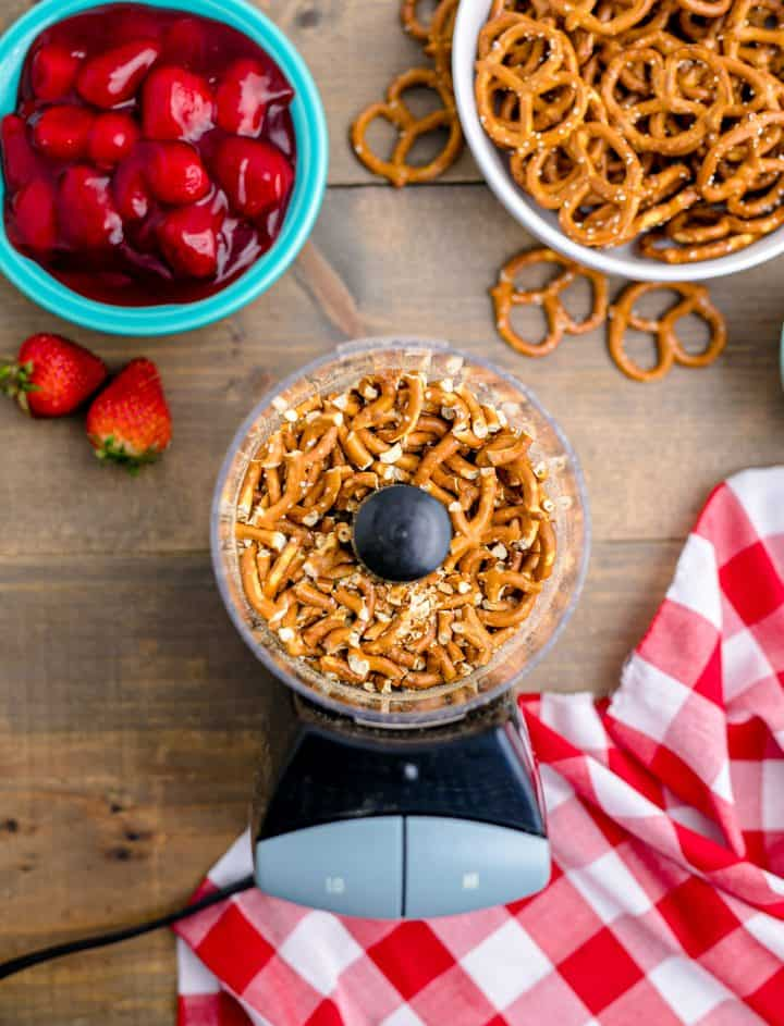 Overhead of pretzels in food processor on wooden table.