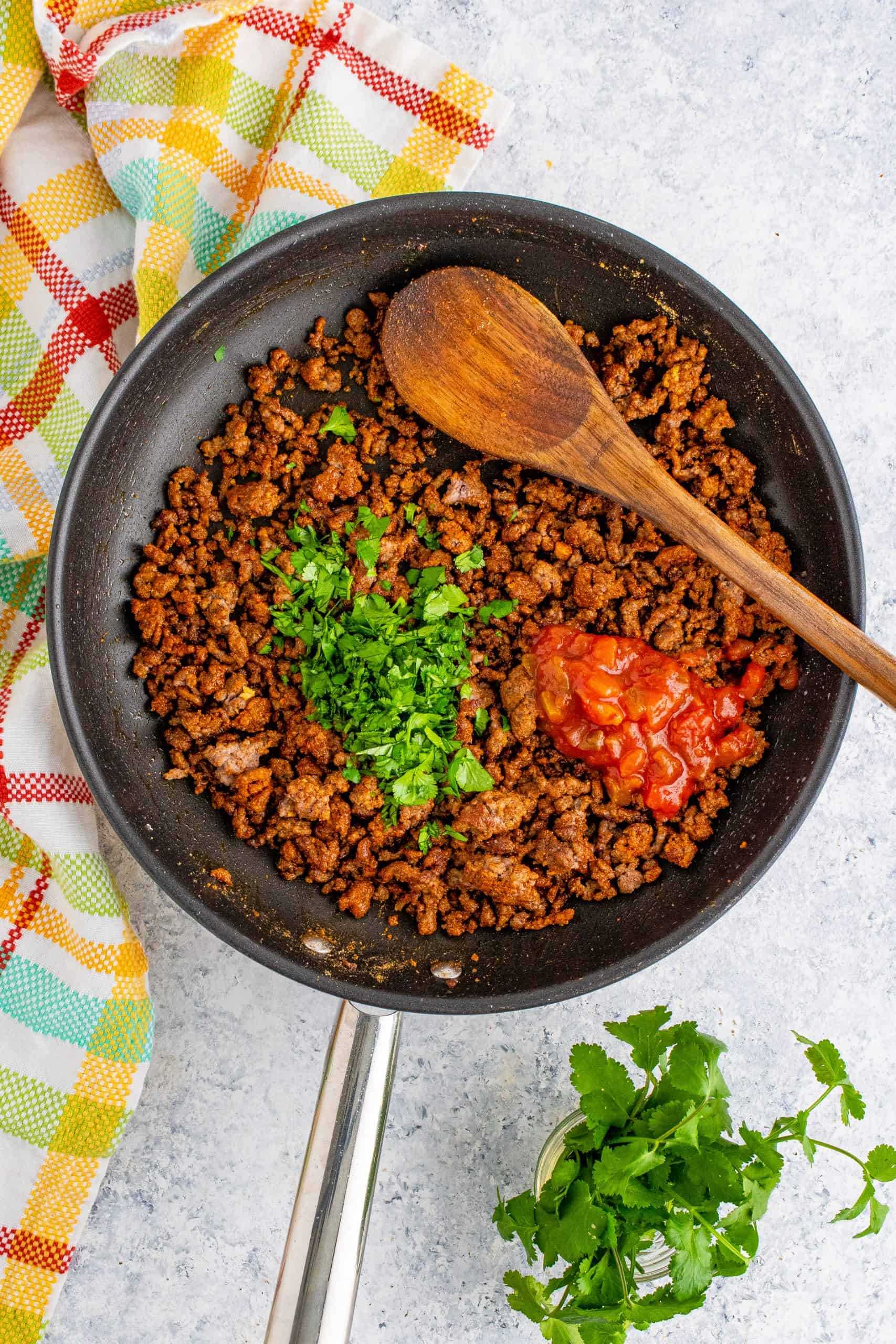 Water, salsa, and cilantro added to ground beef mixture
