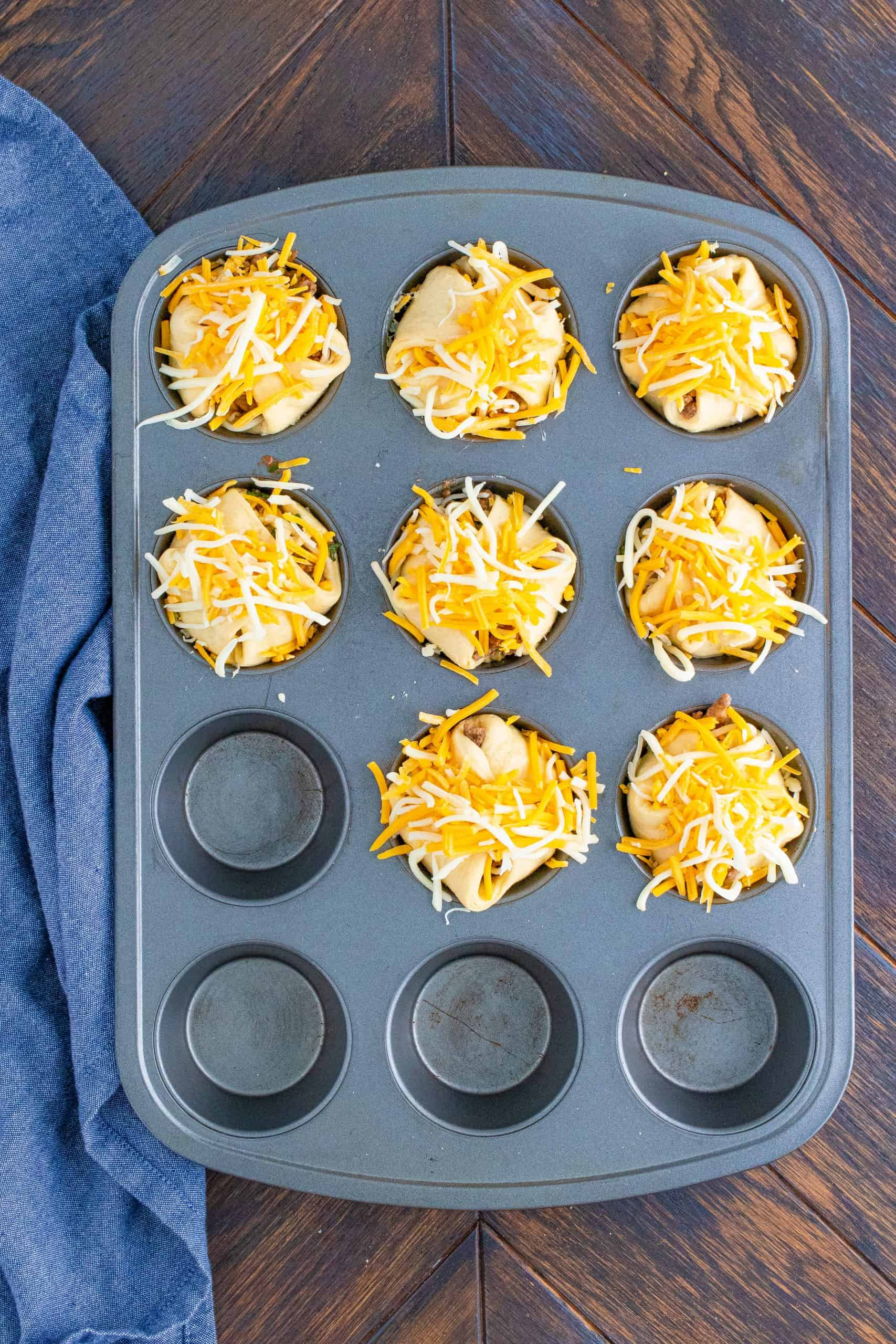 More cheese added to wrapped Taco Cups in muffin tin.