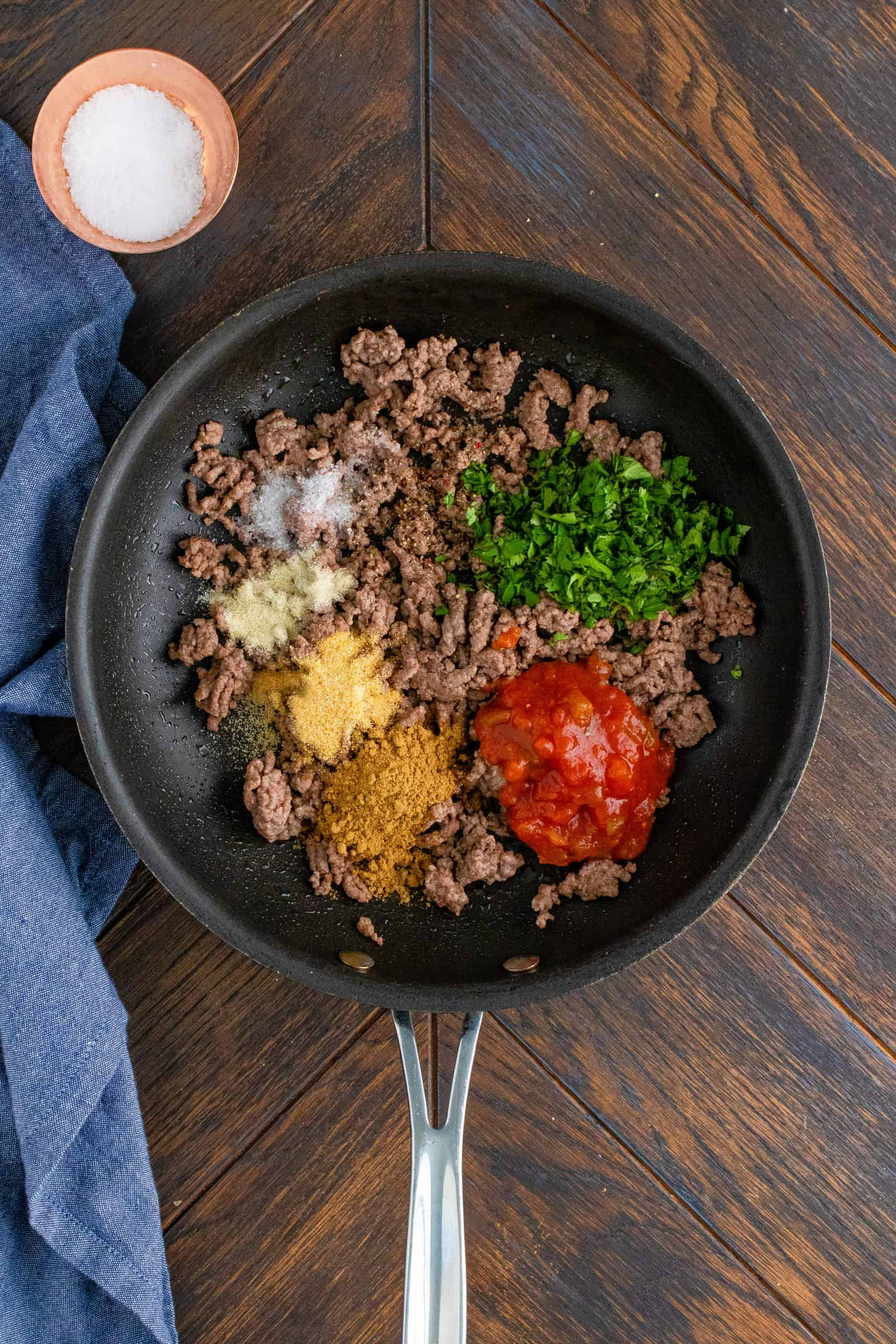 Cumin, garlic powder, onion powder, salt, pepper, salsa, water, and cilantro added to cooked ground beef in pan with blue linen on the side.