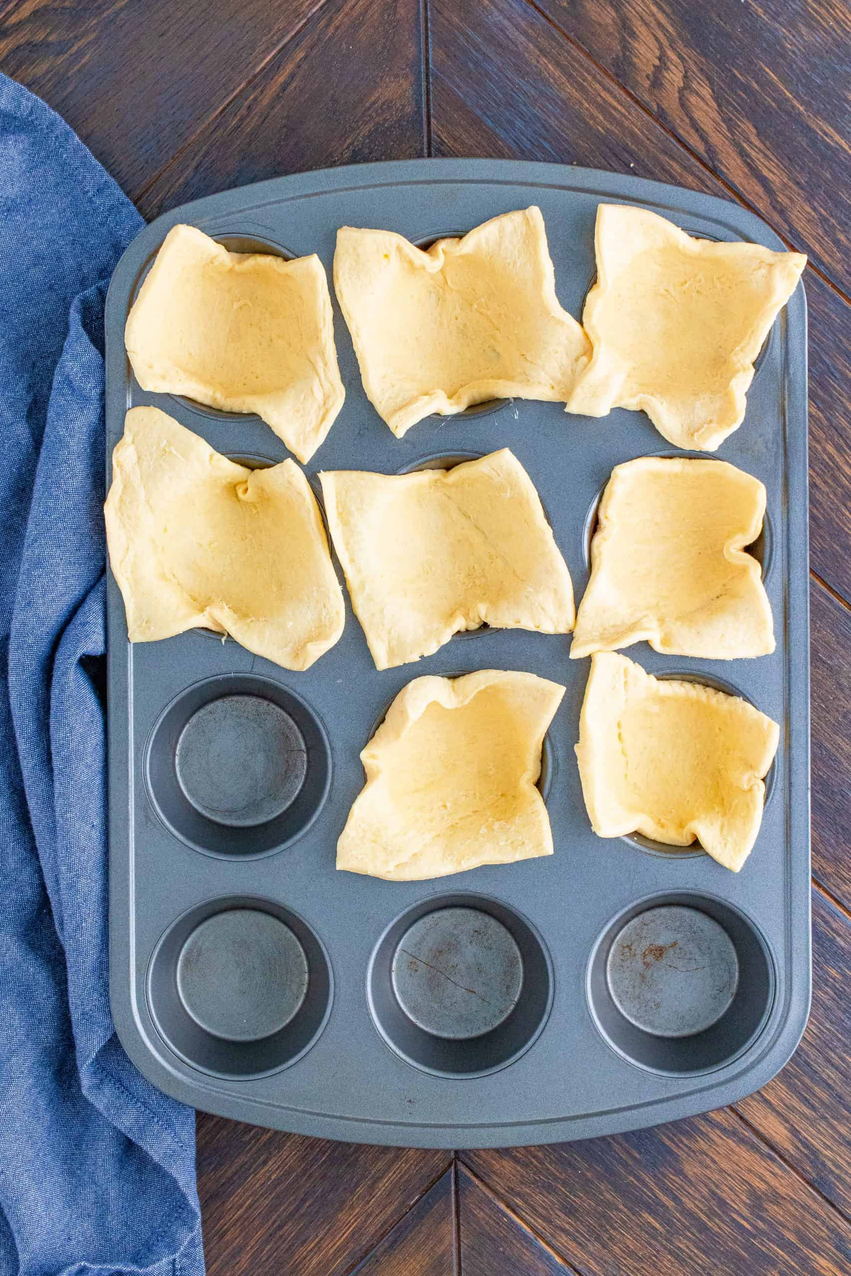 Cut Crescent dough placed into wells of a muffin tin.