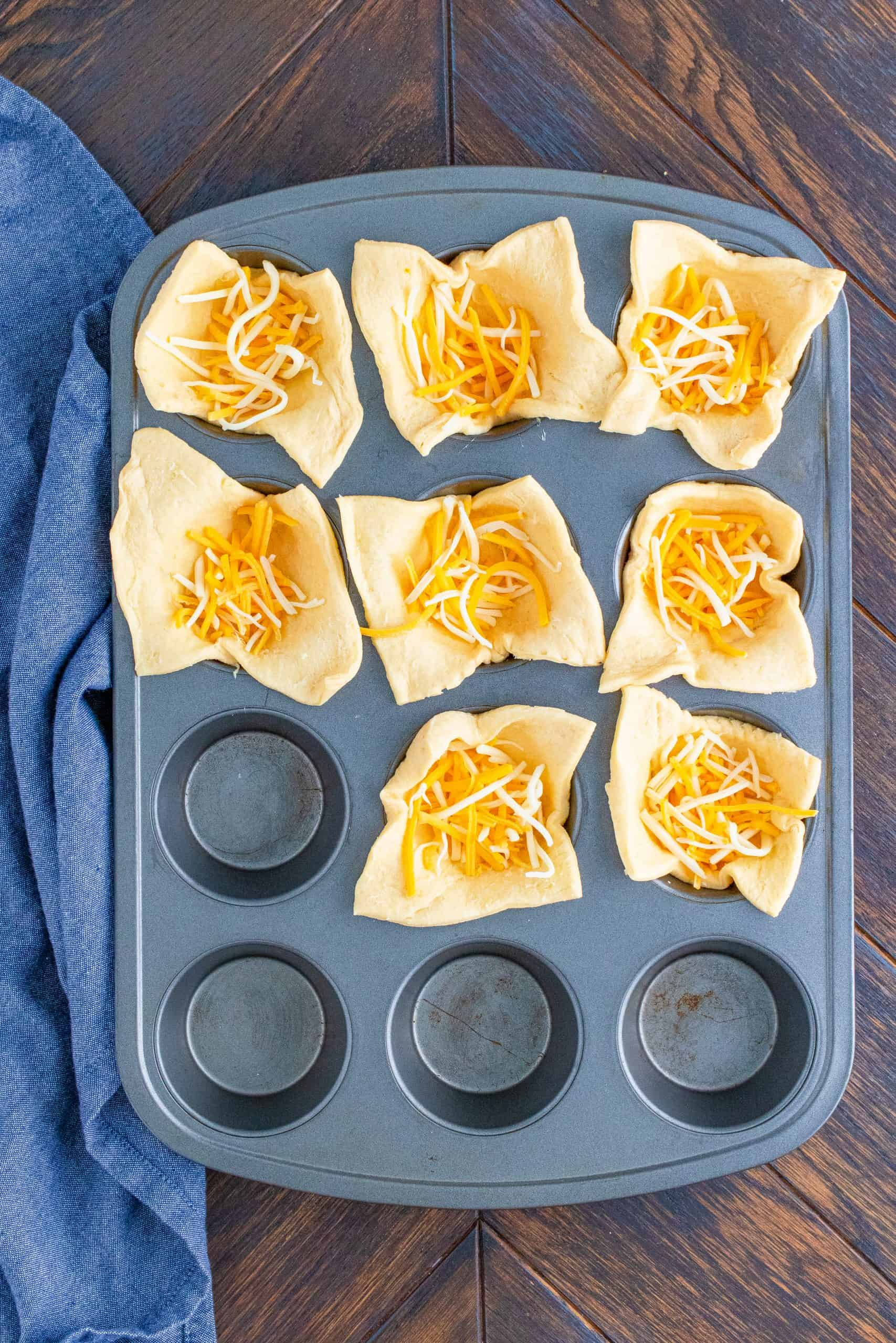 Shredded cheese added to the crescent dough in muffin tin.
