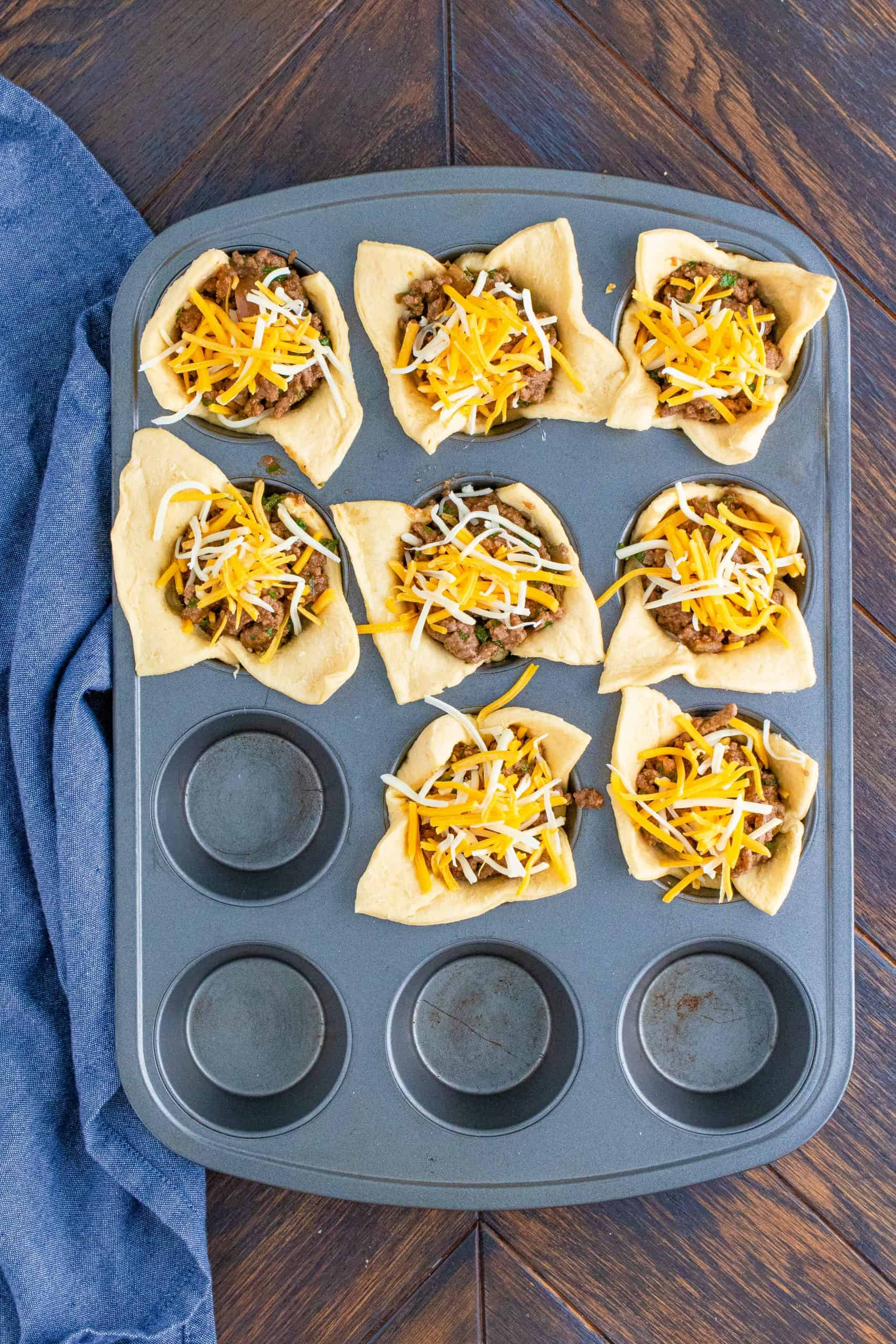 More cheese topping the taco meat in muffin tin.