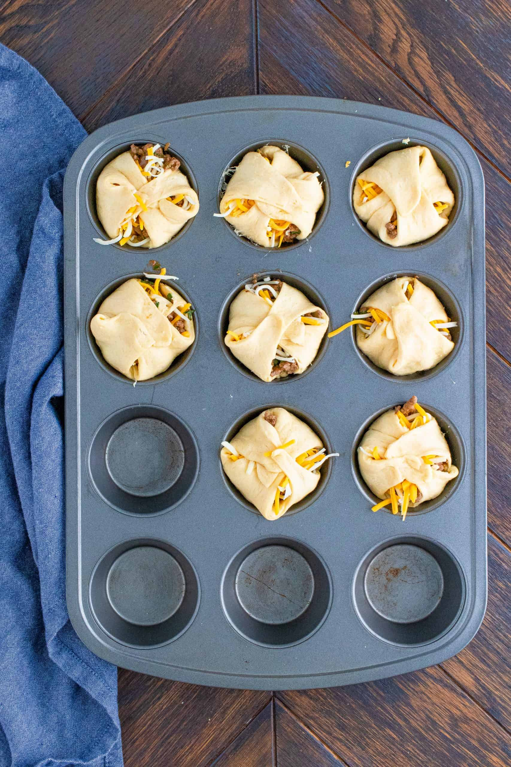 Crescent dough wrapping all fillings up in muffin tin.