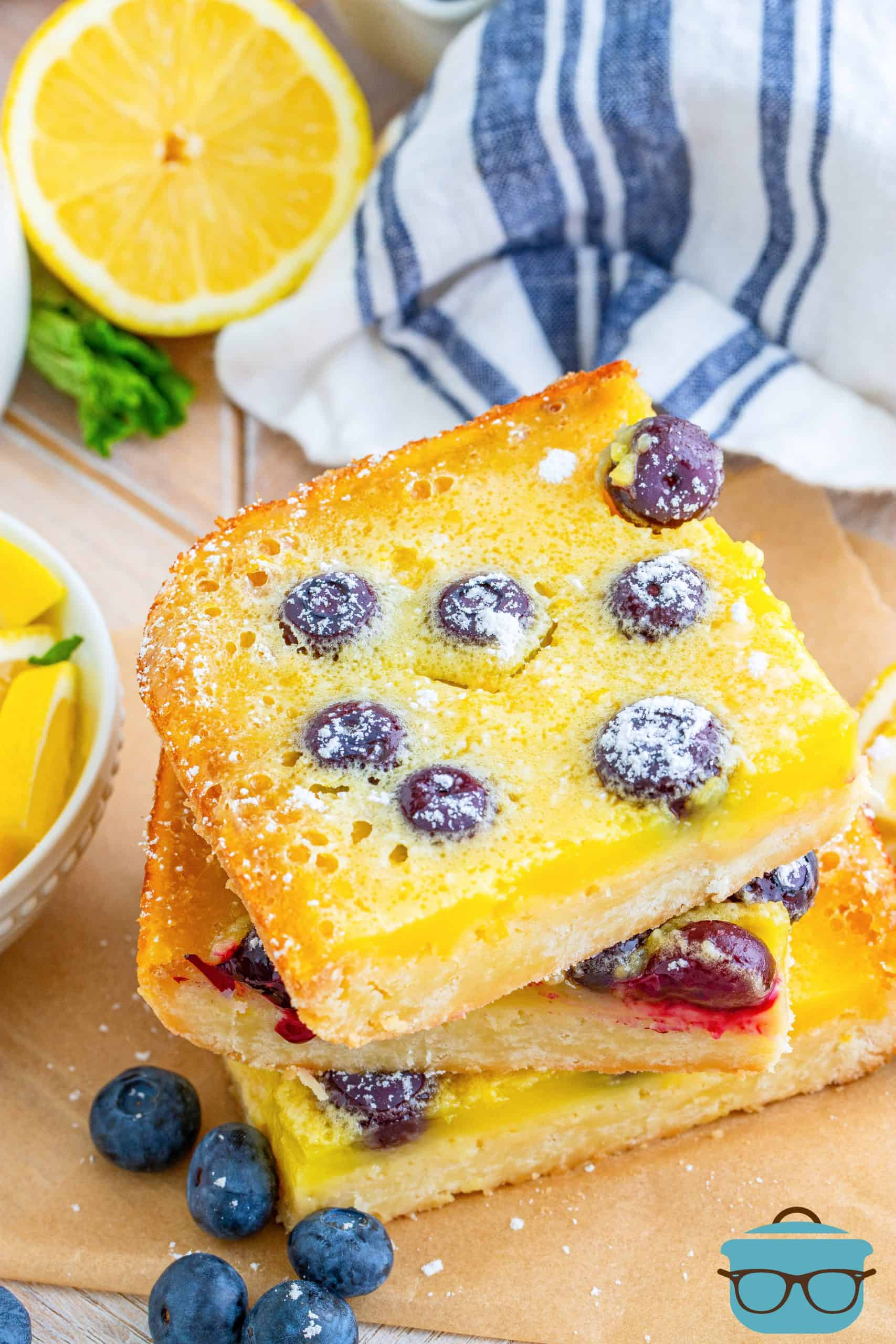 Overhead photo fo stacked Blueberry Lemon bars surrounded by blueberries on wooden board.