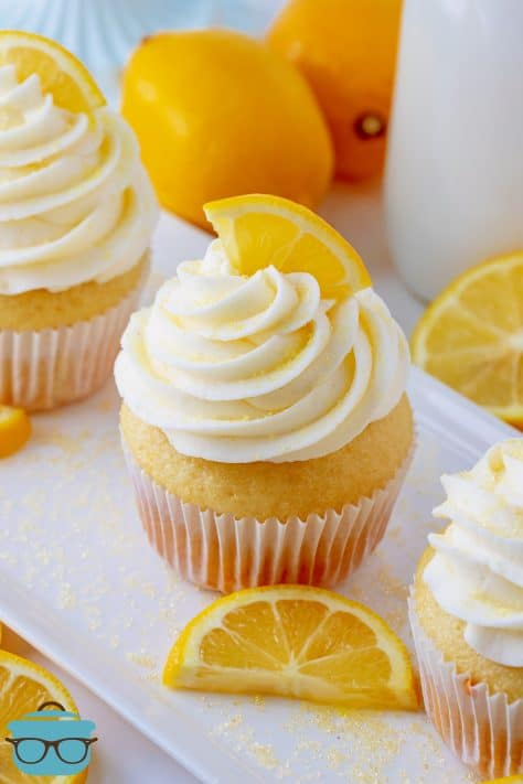 Close up of one Homemade Lemon Cupcake on white patter with lemons in background