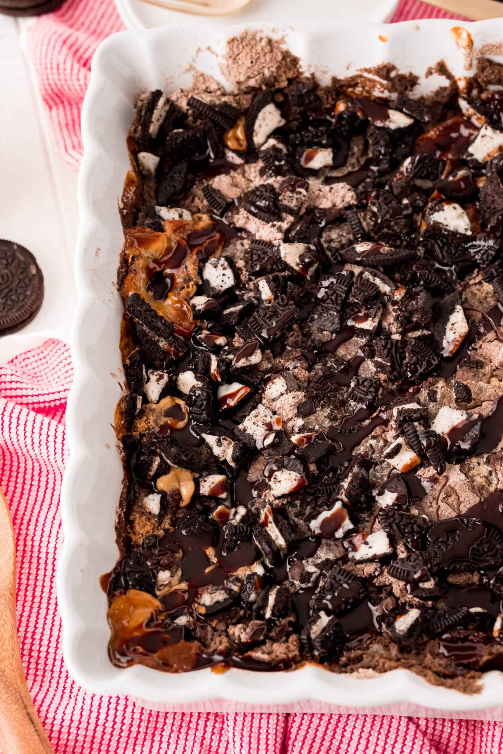 Finished Oreo Dump Cake Recipe out of oven in pan with a red and white kitchen towel underneath.
