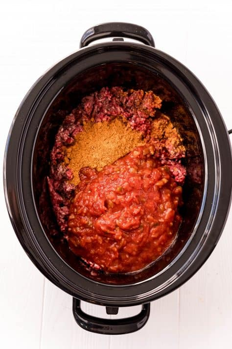 Salsa and taco seasoning added to black crock pot with ground beef
