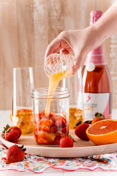 Orange juice being poured into jar with diced strawberries
