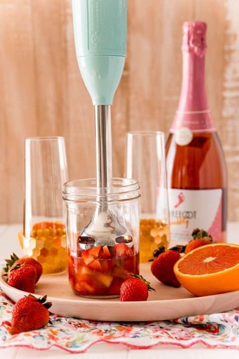 Immersion blender blending together strawberries and orange juice
