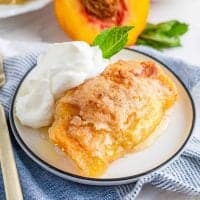 Square image of Easy Fresh Peach Dumplings with whipped cream and mint