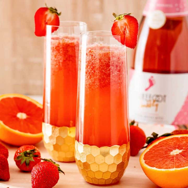 Square image of mimosas with strawberry garnish on glasses