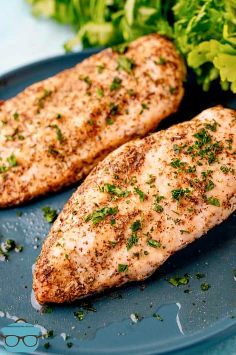 Finished Air Fryer Chicken Breasts topped with parsley on grey plate
