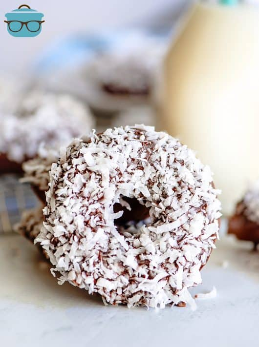 Propped up Chocolate Coconut Baked Donut showing coconut with milk in background
