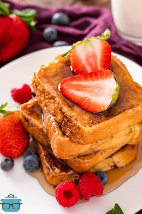Stacked Brioche French Toast on white plate topped with strawberries and syrup