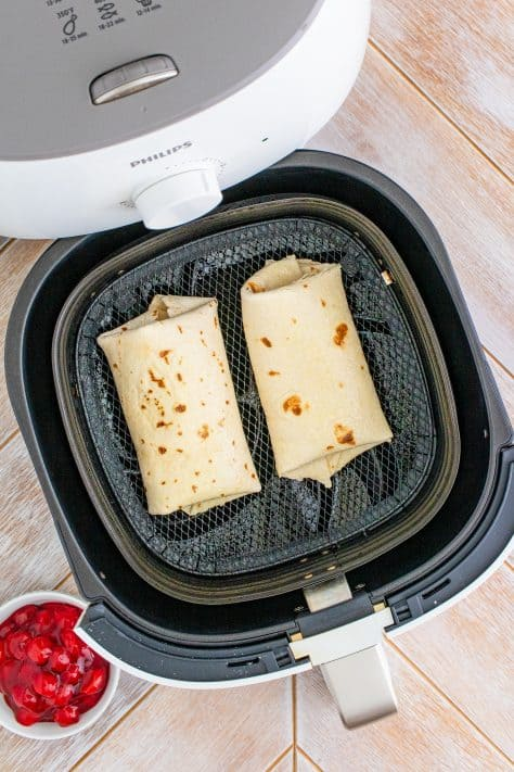 Two Chimichangas in air fryer basket
