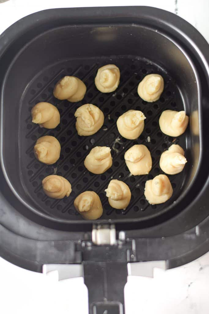 uncooked churro bites shown in an air fryer basket