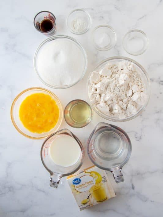 Ingredients needed: all-purpose flour, granulated sugar, baking powder, baking soda, salt, vanilla extract, eggs, milk, water, vegetable oil, banana pudding, milk, unsalted butter, almond extract, powdered sugar