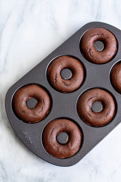 Baked donuts in donut pan overhead image