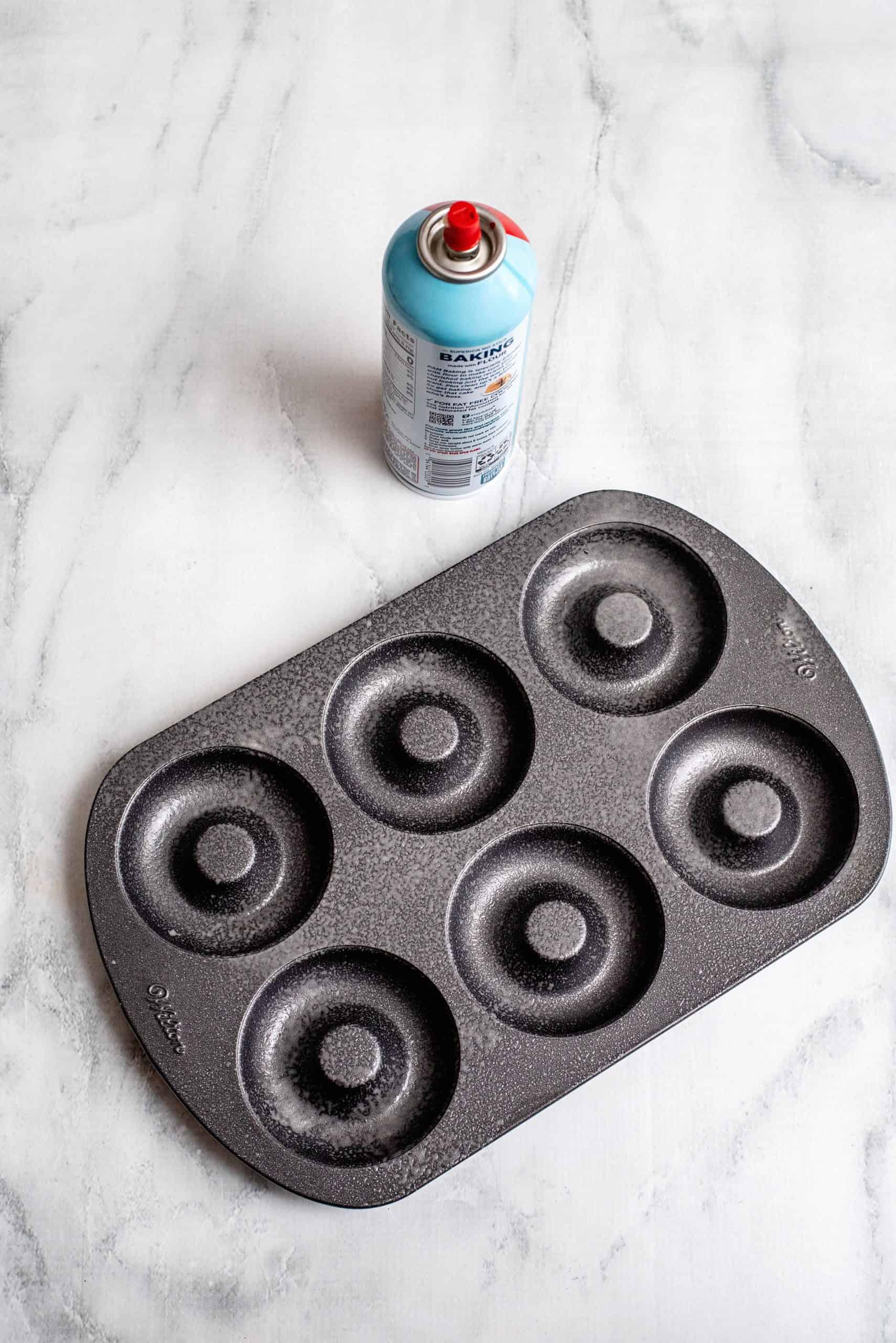 Donut pan sprayed with cooking spray