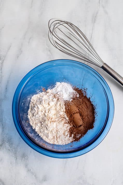 Dry ingredients added to blue bowl with whisk