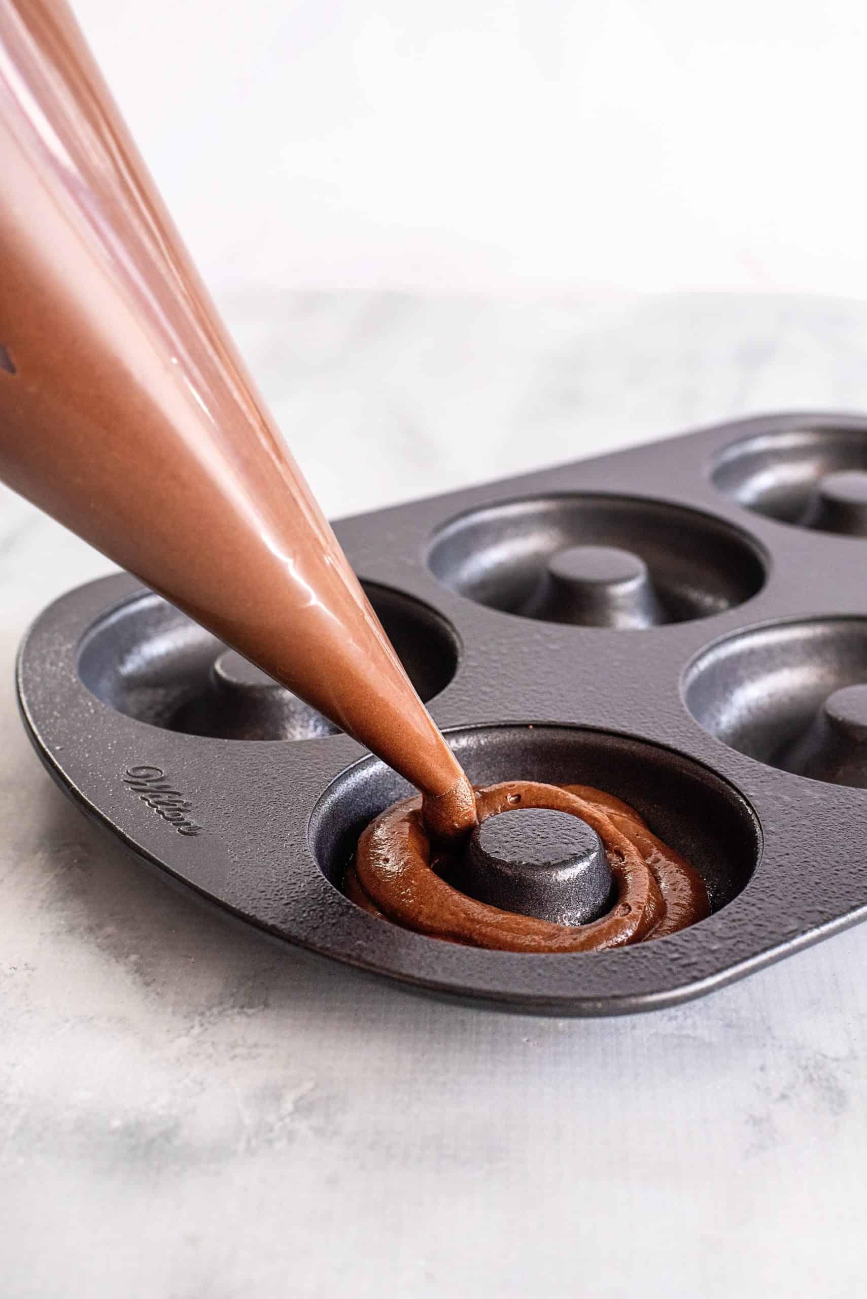 Piping bag piping donut batter into prepared donut pan