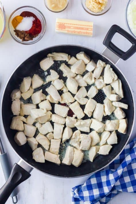 Chicken in pan cooked surrounded by other ingredients