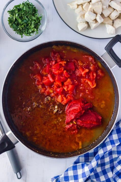 Diced tomatoes, tomato paste and chicken broth added to skillet not stirred.