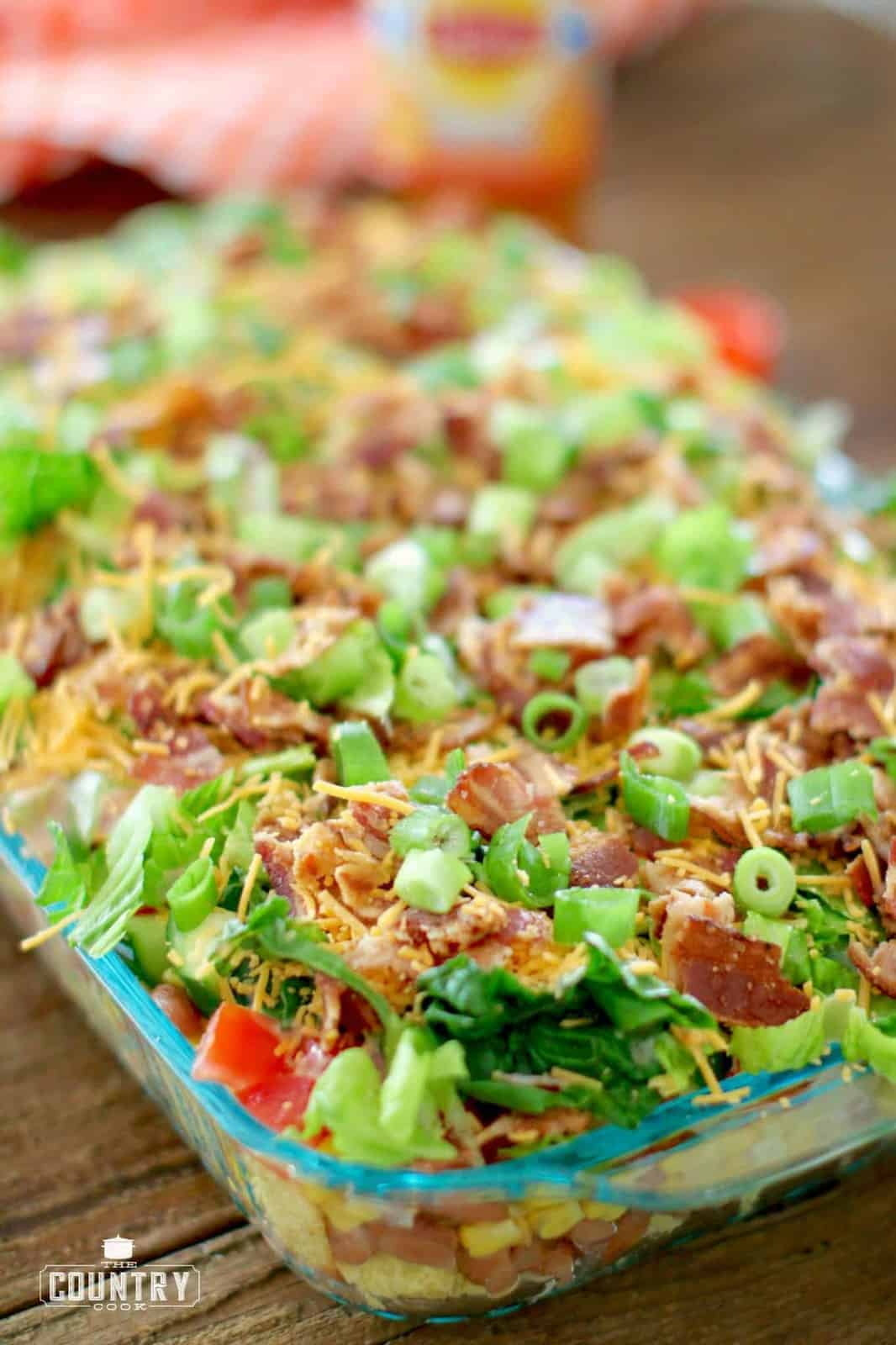 romaine lettuce, chopped bacon and green onions layered at the very top of the cornbread salad in a baking dish.