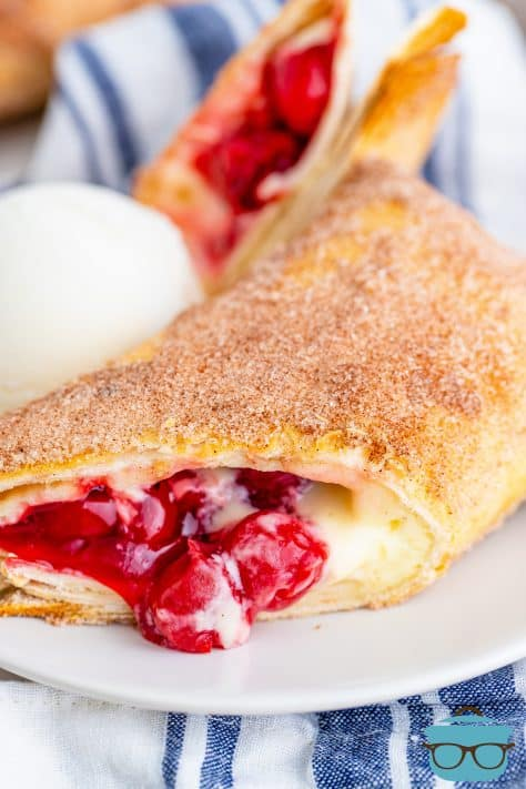 Air Fryer Cheesecake Chimichanga on plate cut open showing cherry cheesecake filling