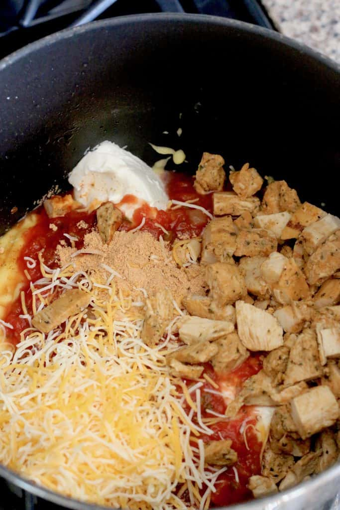 cooked spaghetti, diced cooked chicken, salsa, taco seasoning and shredded cheese shown in the bottom of a black pot
