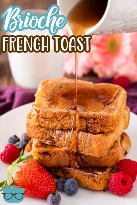 Stacked Brioche French Toast with syrup being poured over it on white plat with fruit Pinterest image