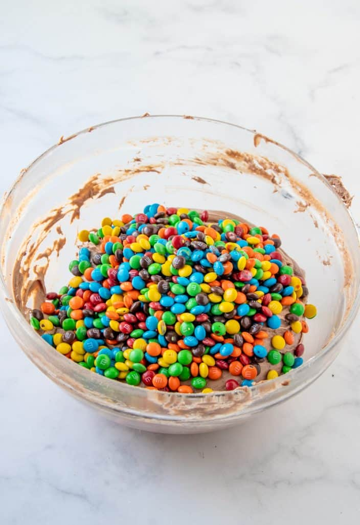 Mini M&M's added to clear bowl with brownie batter mixture