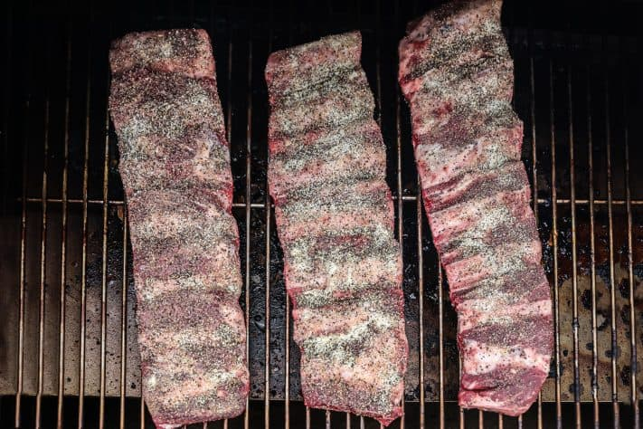 Ribs being placed on the smoker