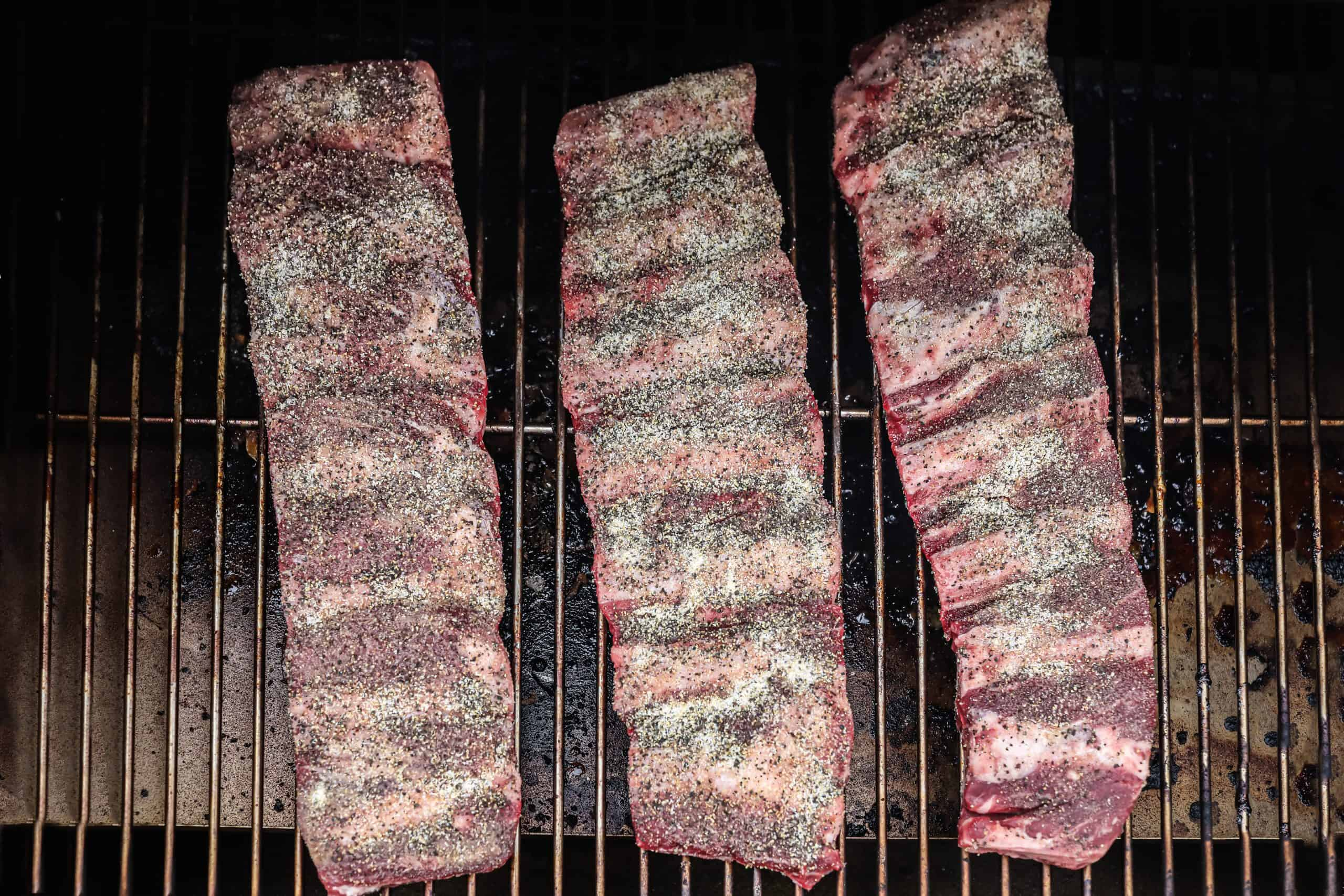 Ribs being placed on the smoker.