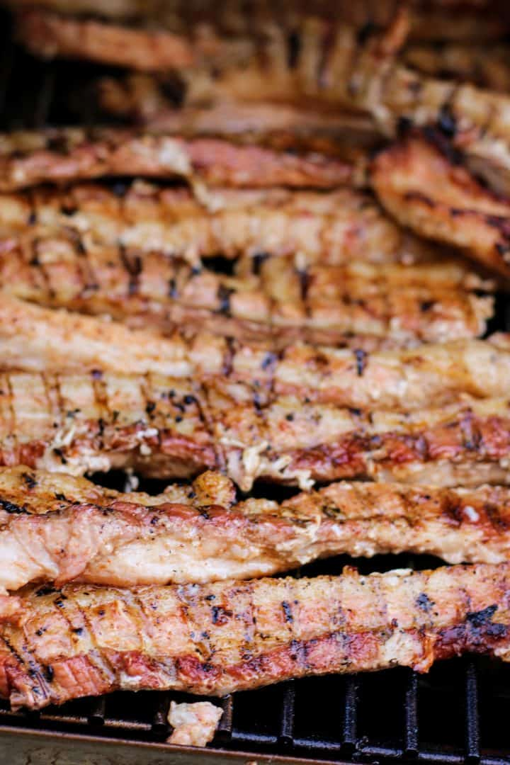 Close up photo of pork belly on smoker after flipping