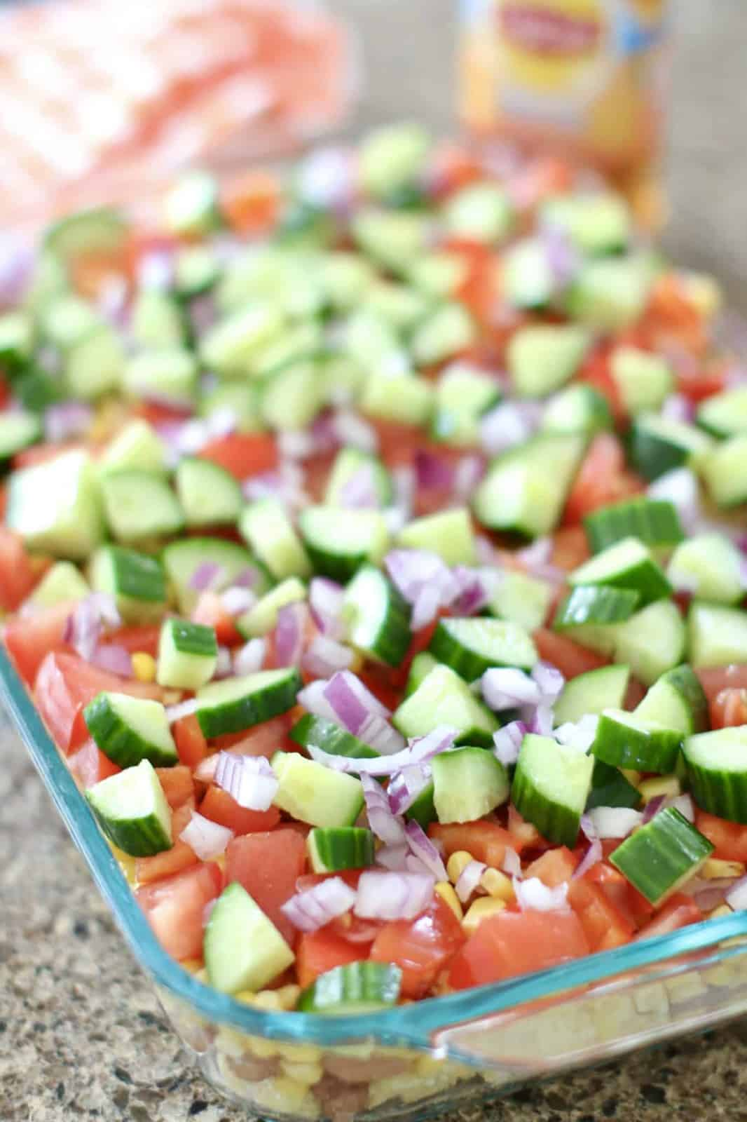 pinto beans, corn, tomatoes, onions and cucumbers layered on top of cubed cornbread in a baking dish.