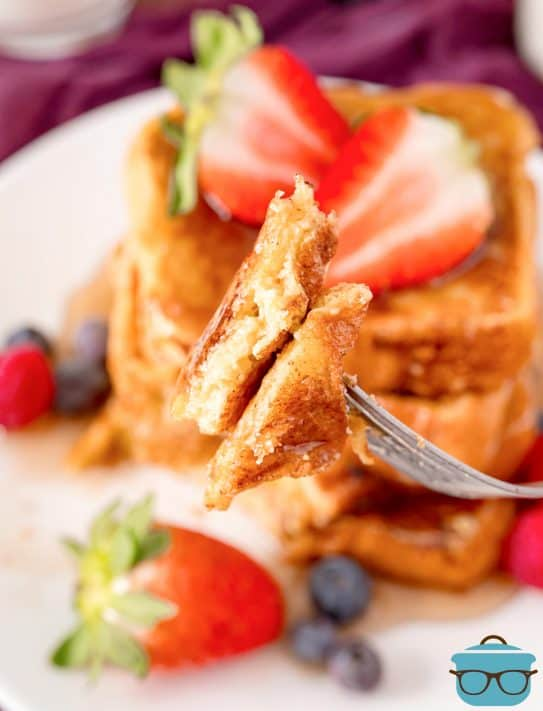 Fork holding some of the French toast with stack of them in background