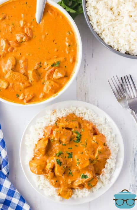 Overhead photo of Creamy Butter Chicken on plate with rice and chicken and rice in the background