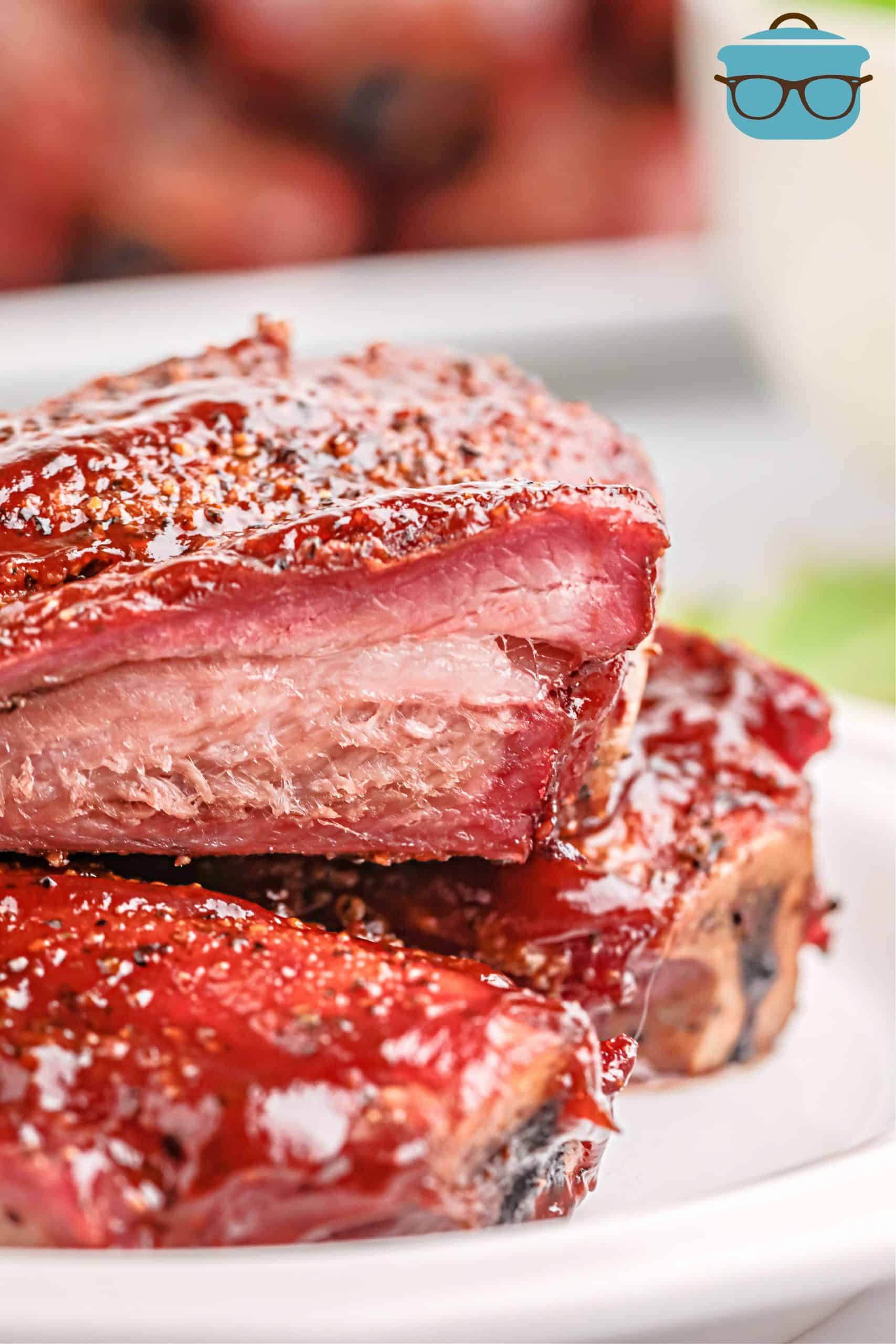 Close up of Ribs stacked on plate showing smoke ring.