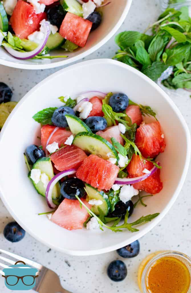 Bowl with Watermelon Feta Salad in it with another bowl behind it and ingredient garnish beside