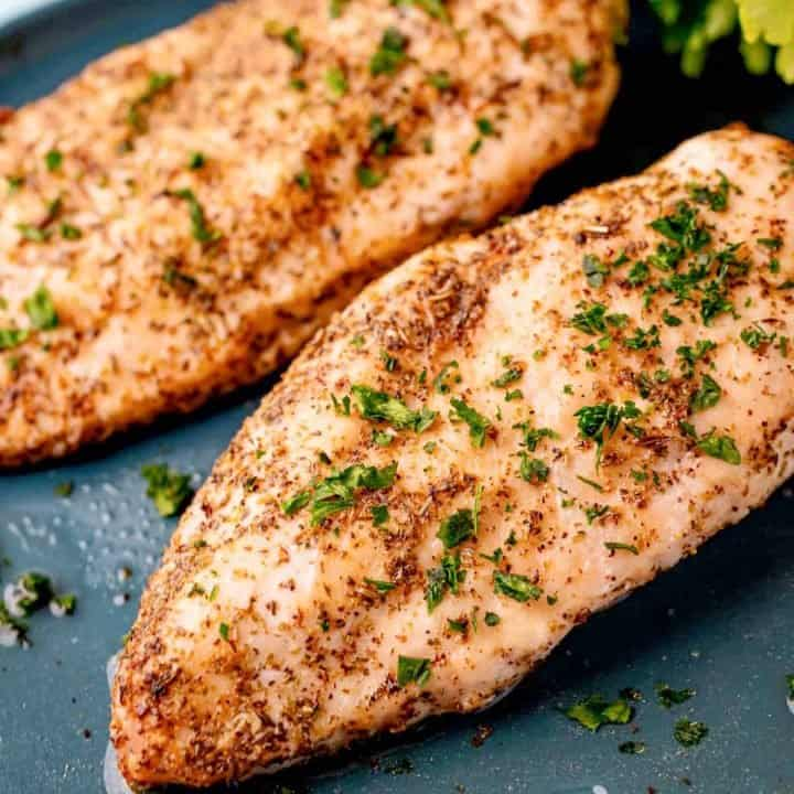 Square image close up of finished Air Fryer Chicken Breasts on gray plate topped with parsley