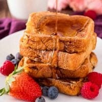 Square photo of syrup being poured over Brioche French Toast on white plate with fruit
