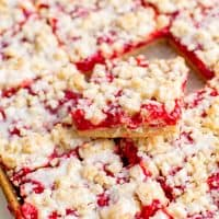 Square image of Cherry Crumble Bar Recipe in pan with one bar sticking out the top stacked