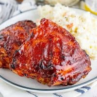 Close up of finished Grilled BBQ Chicken Thigh Recipe on plate with side dish square image
