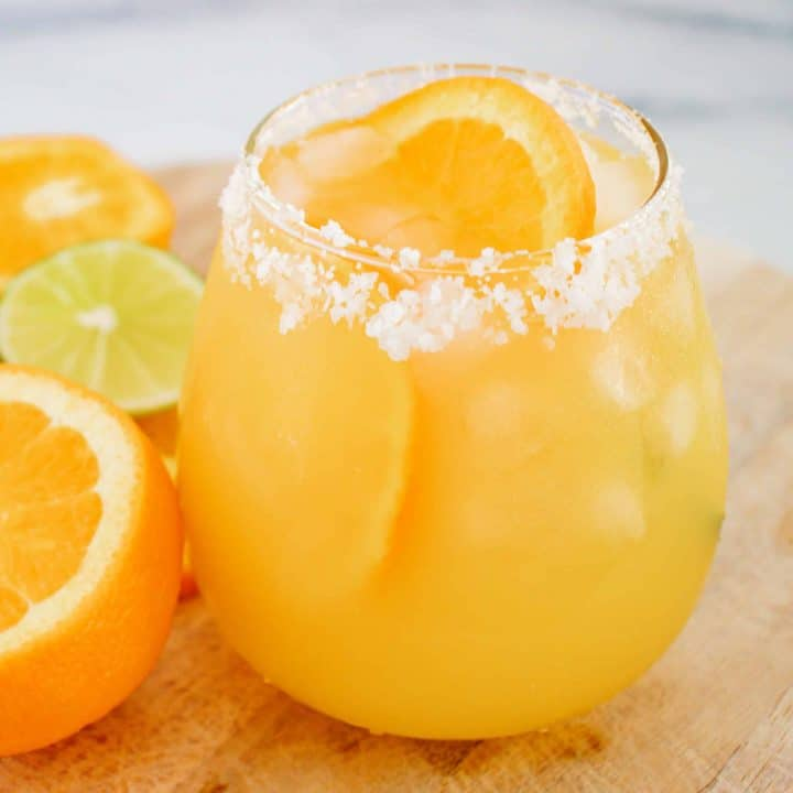 Close up square image of finished Margarita in glass with salt rim and orange slice